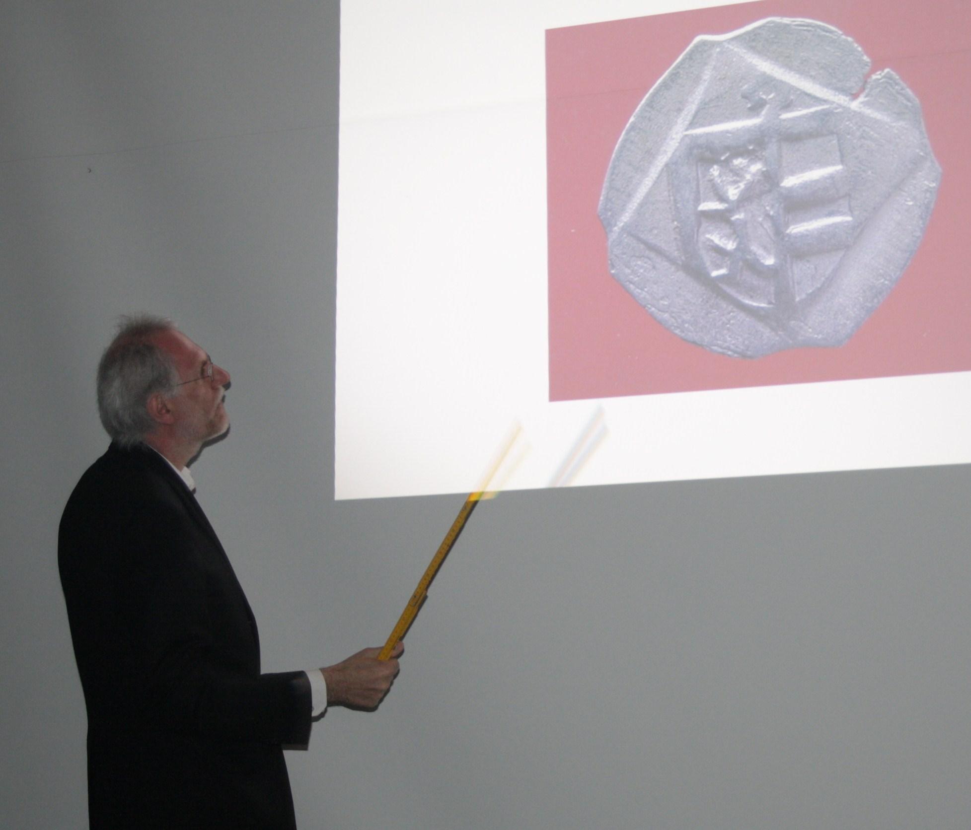 Prof. Emmerig zeigt einen Salzburger Pfennig aus dem Münzfund von Scheibbs